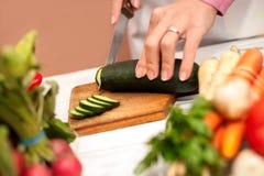 Τεμαχισμός του αγγουριού με ένα μαχαίρι στοκ φωτογραφία με δικαίωμα ελεύθερης χρήσης