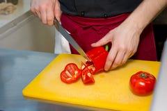 Τεμαχισμός του γλυκού πιπεριού στον ξύλινο τέμνοντα πίνακα αρσενικά χέρια που κόβονται με το μεγάλο κόκκινο πιπέρι κουδουνιών μαχ στοκ εικόνες