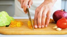 Τεμαχισμός του γλυκού πιπεριού στον ξύλινο τέμνοντα πίνακα απόθεμα βίντεο