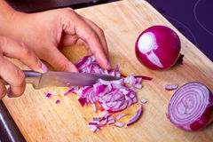 Τεμαχισμός του κόκκινου κρεμμυδιού στην κουζίνα στοκ εικόνα