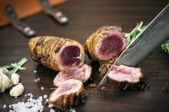 Τεμαχισμός του οργανικού ρόλου βόειου κρέατος ψητού στον ξύλινο πίνακα με τα συστατικά στοκ φωτογραφία