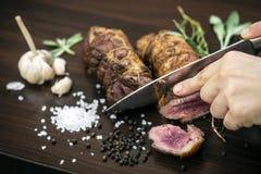 Τεμαχισμός του οργανικού ρόλου βόειου κρέατος ψητού στον ξύλινο πίνακα με τα συστατικά στοκ εικόνες
