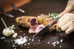 Τεμαχισμός του οργανικού ρόλου βόειου κρέατος ψητού στον ξύλινο πίνακα με τα συστατικά στοκ εικόνα