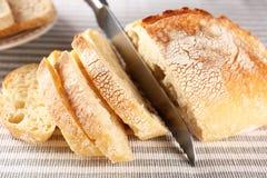 Τεμαχισμός του φρέσκου ψωμιού με το μαχαίρι στο ύφασμα στοκ φωτογραφίες
