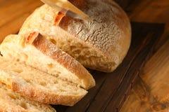 Τεμαχισμός του φρέσκου ψωμιού στον ξύλινο τέμνοντα πίνακα στοκ εικόνα