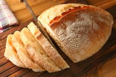 Τεμαχισμός του φρέσκου ψωμιού στον ξύλινο τέμνοντα πίνακα στοκ φωτογραφία