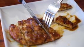 Τεμαχισμός του ψημένου στη σχάρα κοτόπουλου στην εξυπηρέτηση του πιάτου απόθεμα βίντεο