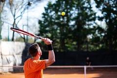 Τενίστας στην πορτοκαλιά εξυπηρέτηση με τη σφαίρα στον αέρα και άλλη στοκ φωτογραφία