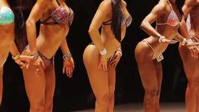 Τεντωμένα θηλυκά bodybuilders που θέτουν στη σκηνή στο μπικίνι, ανταγωνισμός ικανότητας απόθεμα βίντεο