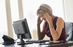 Τεντωμένη επιχειρηματίας που εξετάζει τον υπολογιστή στο γραφείο Στοκ Εικόνες