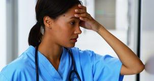 Τεντωμένος θηλυκός γιατρός που στέκεται στο διάδρομο φιλμ μικρού μήκους