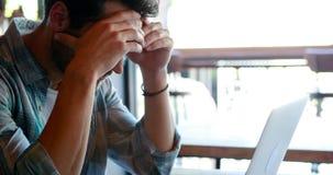 Τεντωμένο άτομο που χρησιμοποιεί το lap-top ενώ έχοντας τον καφέ φιλμ μικρού μήκους