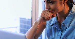 Τεντωμένο θηλυκό εκτελεστικό χρησιμοποιώντας lap-top στο γραφείο 4k απόθεμα βίντεο