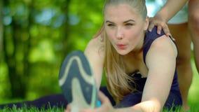 Τεντώνοντας άσκηση υπαίθρια Νέο τέντωμα γυναικών στο πάρκο απόθεμα βίντεο