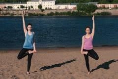 Τεντώνοντας γιόγκα δύο γυναικών που στέκεται στην παραλία από τον ποταμό στην πόλη όμορφη όψη πόλεων Η ισορροπία θέτει στοκ εικόνες με δικαίωμα ελεύθερης χρήσης