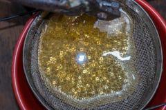 Τεντώστε το χυμένο μέλι μέσω ενός κόσκινου Φιλτράροντας ακατέργαστο μέλι Έκχυση μελιού μέσω ενός κόσκινου από τον εξολκέα μελιού Στοκ Φωτογραφία