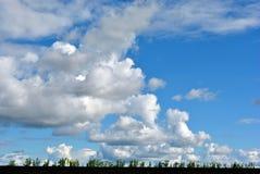 Τεράστια χνουδωτά σύννεφα σε έναν μπλε ουρανό άνοιξη πέρα από έναν οργωμένο τομέα Στοκ Εικόνα