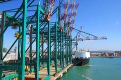 Τεράστιοι γερανοί ατσάλινων σκελετών χειρισμού εμπορευματοκιβωτίων σε ένα τερματικό εμπορευματοκιβωτίων Υπόβαθρο φορτηγών πλοίων  στοκ φωτογραφίες