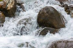 Τεράστιοι υγροί βράχοι σε ένα ρεύμα του βραστού νερού Στοκ Φωτογραφίες