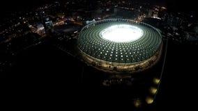 Τεράστιος αθλητικός χώρος που λάμπει με τα φω'τα στην καρδιά megalopolis νύχτας, εναέριος πυροβολισμός απόθεμα βίντεο
