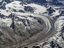 Τεράστιος παγετώνας υψηλών βουνών: η γλώσσα πάγου moraine κάμπτει μεταξύ των χιονοσκεπών αιχμών βουνών και το τόξο κατεβαίνει στη Στοκ Εικόνες