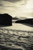 Τεράστιος παφλασμός κυμάτων νερού ενάντια στη σκιαγραφία του blockhouse στο χρυσό ουρανό ηλιοβασιλέματος σε γραπτό Στοκ φωτογραφία με δικαίωμα ελεύθερης χρήσης