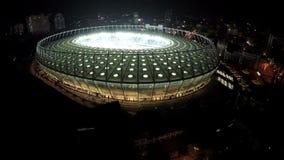 Τεράστιος φωτισμένος χώρος ποδοσφαίρου, εναέρια άποψη, παίκτες που παίζει τον αγώνα στο στάδιο απόθεμα βίντεο