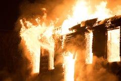 Τεράστιο αποσπώντας σπίτι φλογών στην πυρκαγιά άτομο που ελέγχει τον πυροσβεστήρα Στοκ Εικόνες