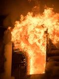 Τεράστιο αποσπώντας σπίτι φλογών στην πυρκαγιά άτομο που ελέγχει τον πυροσβεστήρα Στοκ Φωτογραφίες