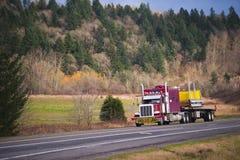 Τεράστιο κλασικό αμερικανικό ημι φορτηγό με πέρα από το διαστατικό φορτίο Στοκ Φωτογραφίες