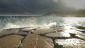 Τεράστιο σπάσιμο κυμάτων στα παράκτιους δραματικούς σύννεφα και τον ήλιο απότομων βράχων φιλμ μικρού μήκους