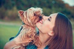 Τεριέ του Γιορκσάιρ Ένα κορίτσι με τα μακρυμάλλη αγκαλιάσματα ένα τεριέ του Γιορκσάιρ φυλής σκυλιών έξω στοκ εικόνες