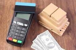 Τερματικό πληρωμής με την πιστωτική κάρτα, το δολάριο νομισμάτων και τα τυλιγμένα κιβώτια στην ξύλινη παλέτα Στοκ εικόνα με δικαίωμα ελεύθερης χρήσης