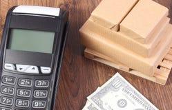 Τερματικό πληρωμής, δολάριο νομισμάτων και τυλιγμένα κιβώτια στην ξύλινη παλέτα Στοκ Εικόνες