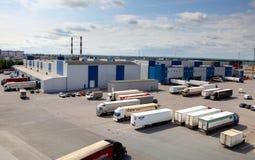 Τερματικό φορτίου σε μια μεγάλη αποθήκη εμπορευμάτων σύνθετη. Τα φορτηγά ξεφορτώνουν, ξεφορτώνοντας ή περιμένοντας στο χώρο στάθμε Στοκ φωτογραφία με δικαίωμα ελεύθερης χρήσης
