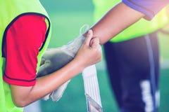 Τερματοφύλακας που φορά τα γάντια στόχου με τον ποδοσφαιριστή στοκ εικόνες