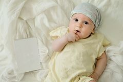 Τετράμηνο παλαιό μωρό με την κενή κάρτα στο κίτρινο φόρεμα στοκ φωτογραφία