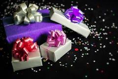 Τετραγωνικά κιβώτια δώρων σε ένα μαύρο εορταστικό υπόβαθρο με τα σπινθηρίσματα Στοκ Φωτογραφία