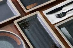 Τετραγωνικά πιάτα του σκοτεινού χρώματος στον πίνακα Στοκ φωτογραφία με δικαίωμα ελεύθερης χρήσης