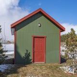 Τετραγωνική μικρή ξύλινη αποθήκευση που ρίχνεται με έναν λαμπτήρα στον πράσινο τοίχο επάνω από την κόκκινη πόρτα στοκ φωτογραφία με δικαίωμα ελεύθερης χρήσης