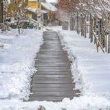 Τετραγωνική ξύλινη διάβαση ανάμεσα στα δέντρα και τα σπίτια στη χαραυγή Γιούτα που αντιμετωπίζεται το χειμώνα στοκ εικόνα