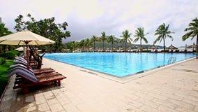 Τετραγωνική πισίνα με το μόνιππο -μόνιππο-longues ομπρελών παραλιών απόθεμα βίντεο