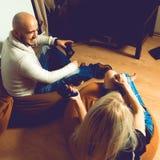 Τετραγωνική φωτογραφία του χαρούμενου ζεύγους που έχει τα παίζοντας παιχνίδια στον υπολογιστή διασκέδασης Στοκ Εικόνα