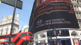 Τετραγωνικό διπλό λεωφορείο καταστρωμάτων τσίρκων Piccadilly και διαφημιστική επιτροπή στο υπόβαθρο απόθεμα βίντεο