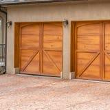 Τετραγωνικό πολυτελές εξωτερικό ενός σπιτιού με τις μοντέρνες καφετιές ξύλινες πόρτες γκαράζ στοκ φωτογραφίες