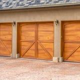 Τετραγωνικό πολυτελές εξωτερικό πλαισίων ενός σπιτιού με τις μοντέρνες καφετιές ξύλινες πόρτες γκαράζ στοκ εικόνες με δικαίωμα ελεύθερης χρήσης