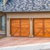 Τετραγωνικό σπίτι εξωτερικό με την γκρίζα και άσπρη στέγη και τις μοντέρνες ξύλινες πόρτες γκαράζ στοκ φωτογραφία με δικαίωμα ελεύθερης χρήσης