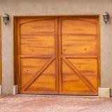 Τετραγωνικό σπίτι πλαισίων εξωτερικό με την γκρίζα και άσπρη στέγη και τις μοντέρνες ξύλινες πόρτες γκαράζ στοκ φωτογραφία