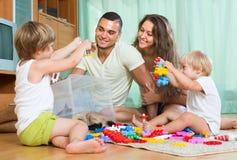 Τετραμελής οικογένεια στο σπίτι με τα παιχνίδια Στοκ Εικόνες