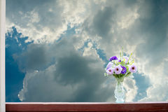 Τεχνητά λουλούδια σε ένα βάζο σε ένα υπόβαθρο ουρανού Στοκ Φωτογραφίες